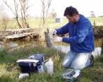 A Waterwatch volunteer conducting a test by a stream