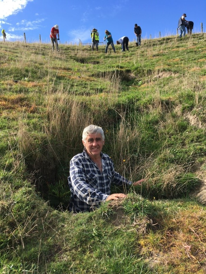 Ian Hasty, standing in a tunnel erosion hole on his property