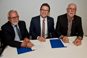 Peter Veenker, Anthony Carbines and Terry Hubbard signing the MOU