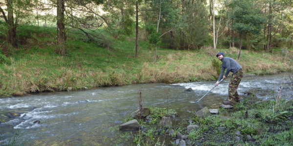 Picture of man completing water quality monitoring
